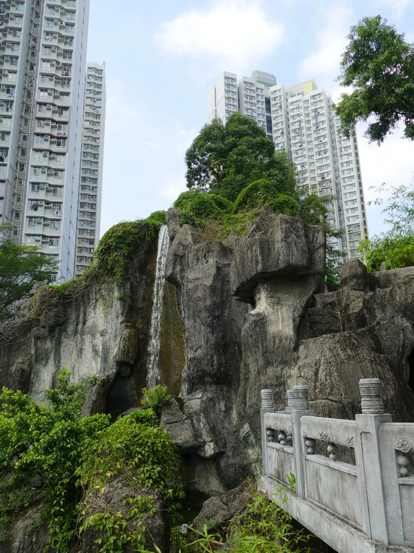 A lovely waterfall against a backdrop of apartment blocks