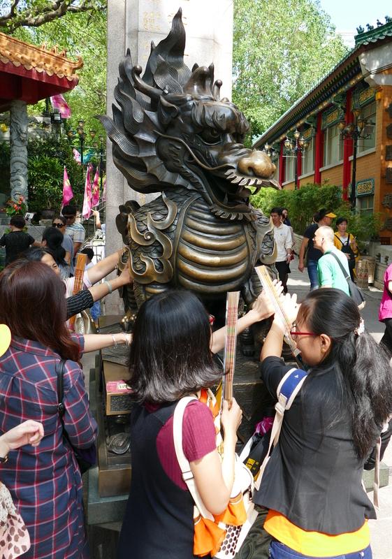 Several people all trying to touch a brass dragon at the entrance to Sik Sik Yuen Temple