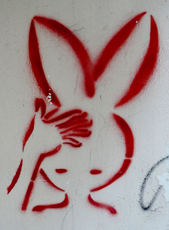 Graffiti image of a man(?) with huge rabbit ears and his hand to his forehead