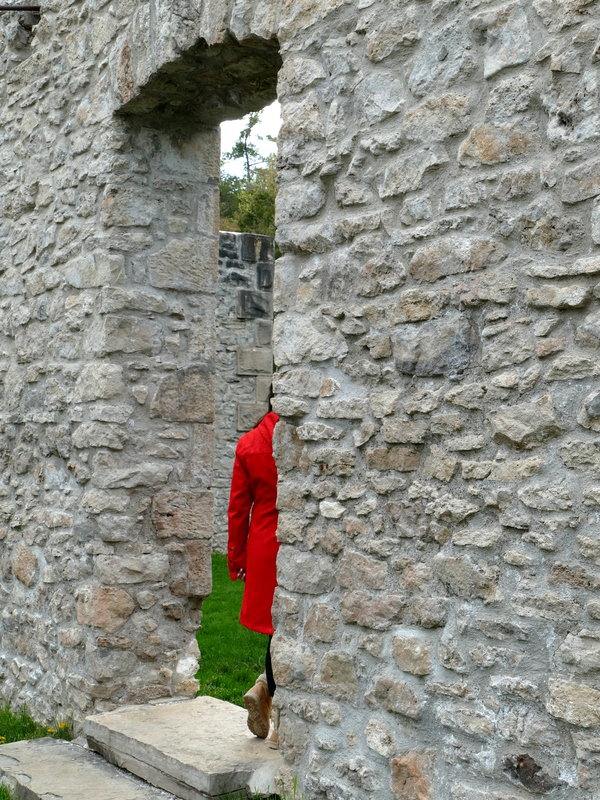 part of a woman and her very red coat framed in a stone doorway