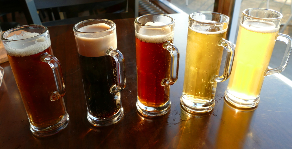 five small beer samples of different colours in miniature tall mugs