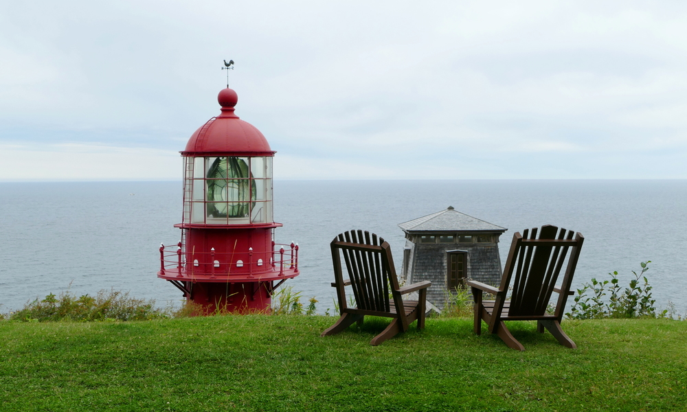 The top of a lighthouse over a hill beside two deck chairs