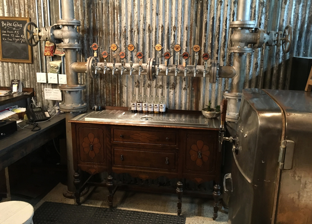 multiple beer taps mounted on a large diameter flanged pipe