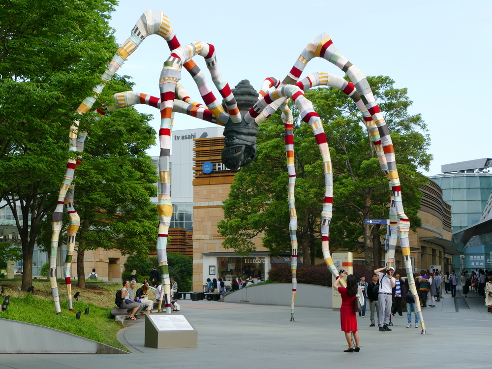 a very large spider-like sculpture, now with multi-coloured fabric leggings in the middle of an outdoor mall