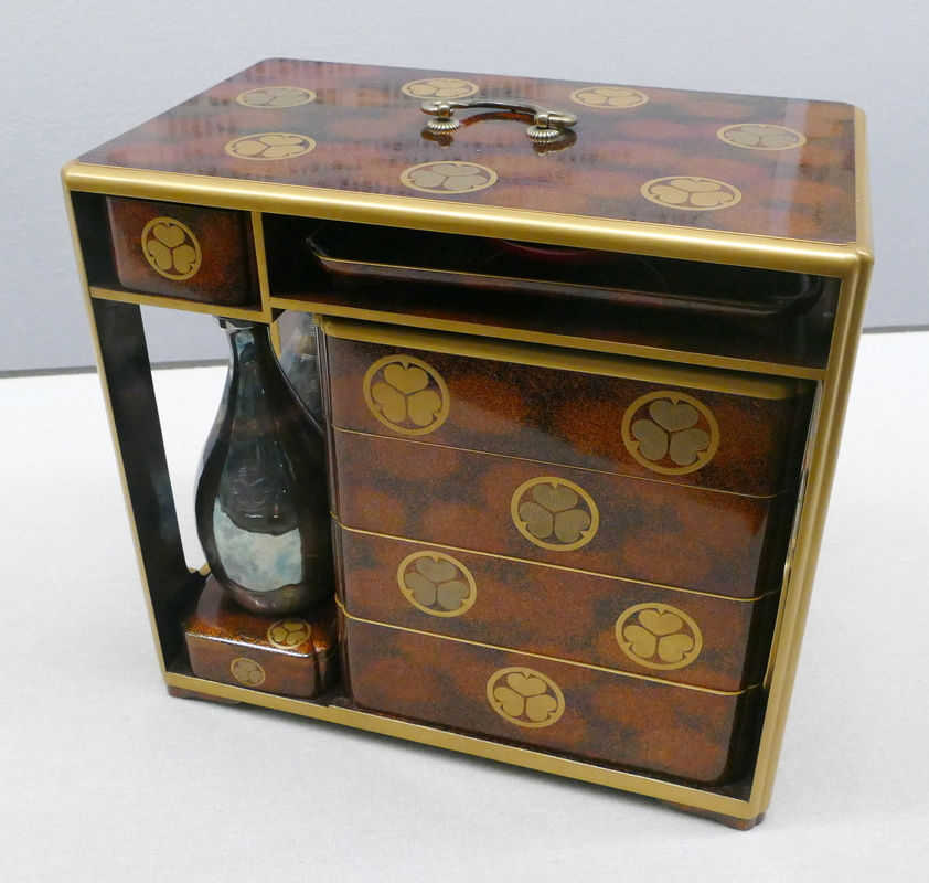 a beautifully lacquered box containing four bento boxes, two sake bottles, and a tray