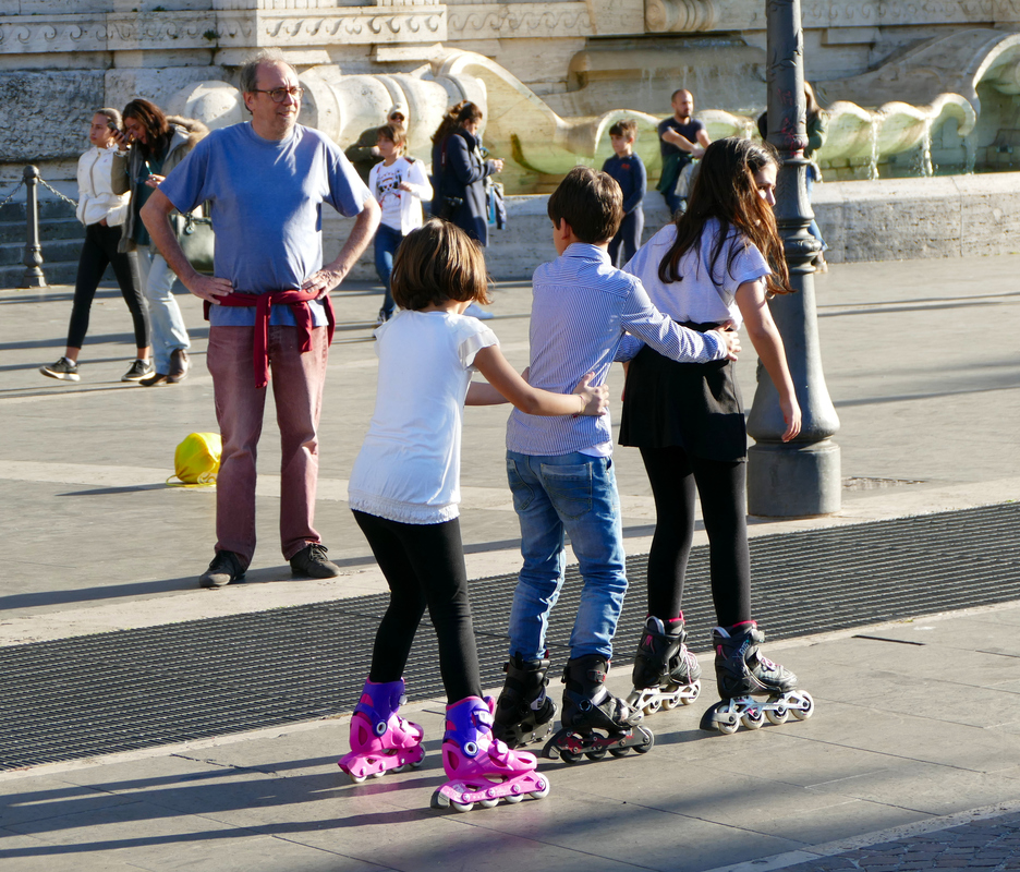 three kids in a row linked to each other and gliding along on rollerblades