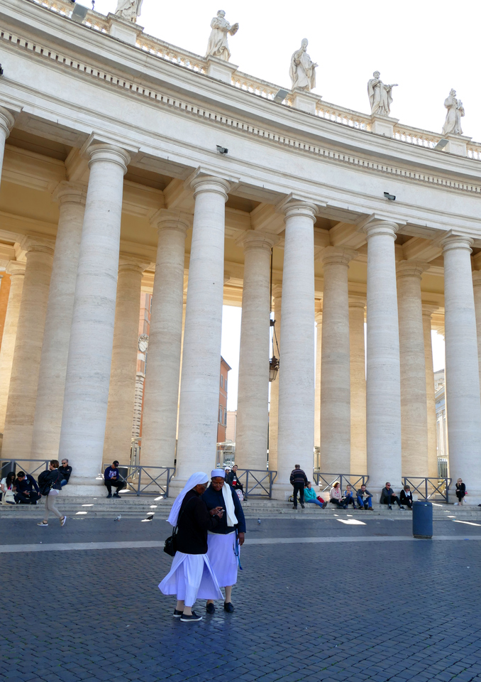 two nuns checking a cellphone as they stand before the columns of St. Peter's Square
