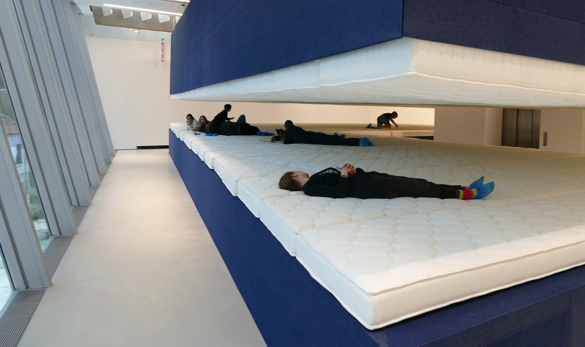 several people lying, and one crawling, between the mattresses