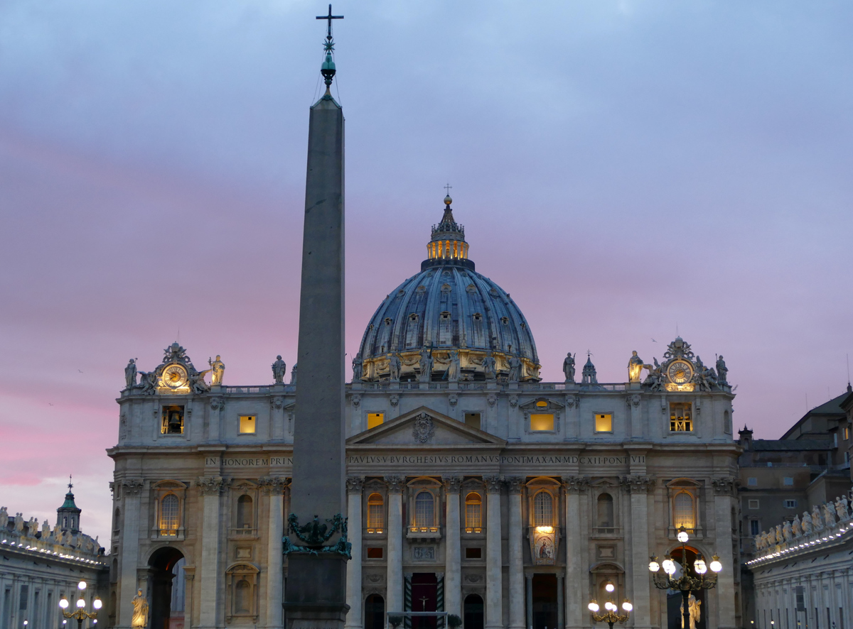 St. Peter's Basilica with the lights coming on and a dusky pink sky behind it