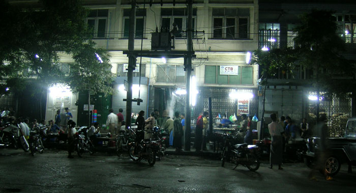 Motorcycles and street vendors at night in Mandalay