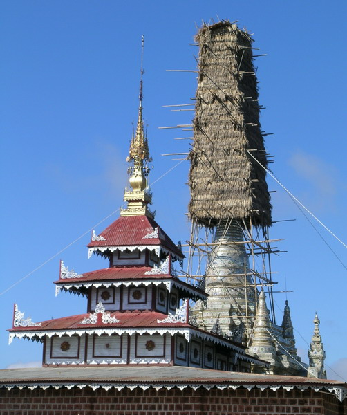 Temple spires, one enclosed in bamboo and thatch.