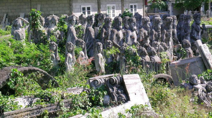 A group of concrete sculptures (possibly intended to be sold as garden decorations?) abandoned and covered in vines.