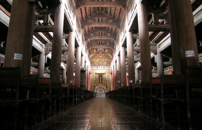 A view down the centre aisle of Phat Diem with massive wood beams supporting the roof