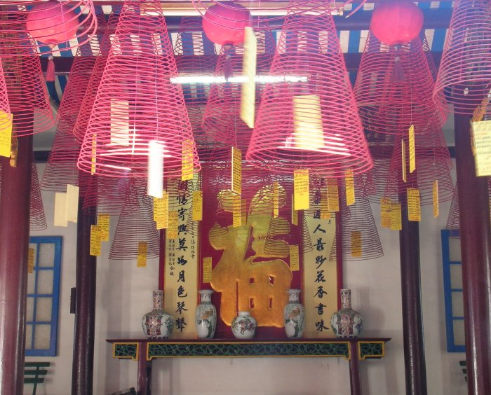 Lots of expanding spirals of red incense hanging from the ceiling of a temple.