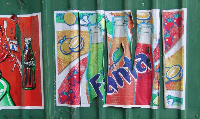 Colourful, peeling Fanta ad on a green corrugated metal wall