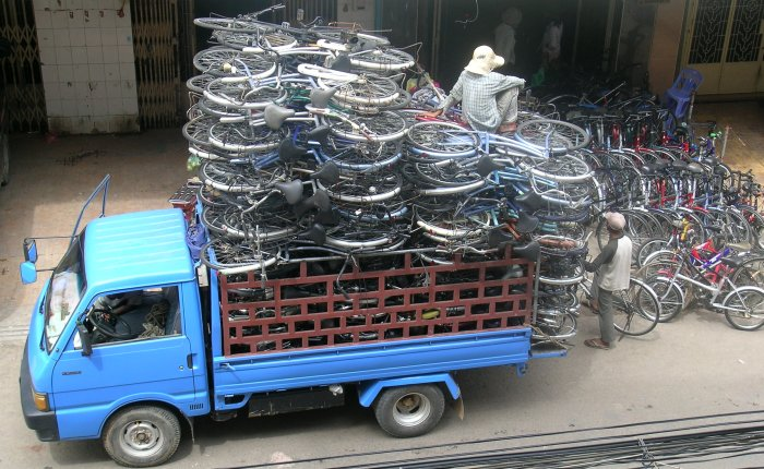 Truck stacked high with bicycles - with a guy sitting on the stack